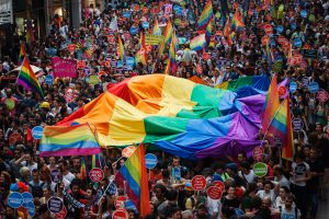 Istanbul, Turkey - June 30, 2013: Thousands of revelers joined for the 11th annual Gay Pride Pride in Taksim, Istanbul showing off a multitude of colorful flags and placards calling for equal rights and justice for LGBT related crime. There were also small protests for other causes.